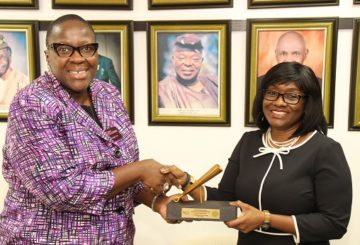 L – R shows Ms. Tinuade Awe, Executive Director, Regulation, The Nigerian Stock Exchange (NSE) presenting a replica of the closing gong to Mrs. Aderonke Adedeji, President, Pension Fund Operators Association of Nigeria and CEO Leadway Pensure during a Closing Gong Ceremony at the Exchange today.
