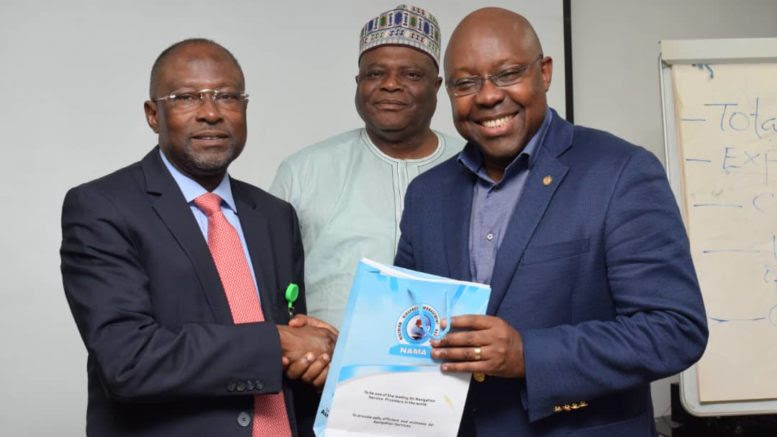 NAMA MD, Capt Fola Akinkuotu (left) presenting a gift to George Uriesi, Chief Operating Officer, Ibom Air, as Director of Finance and Accounts, NAMA, (middle) Aniefiok Umoh looks on.
