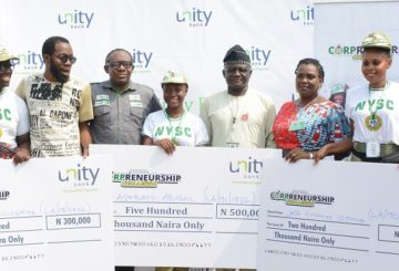 3rd Place winner, Adesina Bolawatife (LA/19C/0702), Principal Consultants, Peeshift, Abiodun Folawiyo, Div Head, Retail Banking, E-business & SME, Unity Bank Plc, Olufunwa Akinmade, Winner of the grand Prize, Miss Adebayo Abigail (LA/19C/1832), Lagos state NYSC Camp Director, Sunday Aroni, Assistant Director, Skills Acquisition & Entrepreneurship Development, Mrs Stella Nweke and 2nd Place winner, Miss Jaja Godgift (LA/19C/1240) CEO of WAPA Apparels, Adetola Adebola during the presentation of prizes to Winners of Unity Bank Corpreneurship Challenge organized in collaboration with the NYSC Skills Development and Entrepreneurship Development, (SAED) at the NYSC Orientation Camp in Lagos.