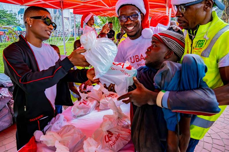 UBA's Brand Ambassador, Wizkid, handing  over food items and other goodies to the helpless and under-privileged at the Food Bank organised by UBA Foundation at the Foundation's Garden and Roundabout in Marina, Lagos on Friday