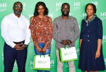 """L-R- Victor Amakwe, Group Head, Private Wealth Management; Christiana Chukwu; Idowu Ilesanmi, both winners in the social media challenge of recitation of National Pledge in Pidgin English; and Cynthia Ndukuba, Head, Head Office Compliance Assurance, Compliance and Transaction Assurance during N1million cheque presentations to four winners of the videos recitation of """"National Pledge"""" in Pidgin English, in celebration of Nigeria @ 60th at the bank's head office."""